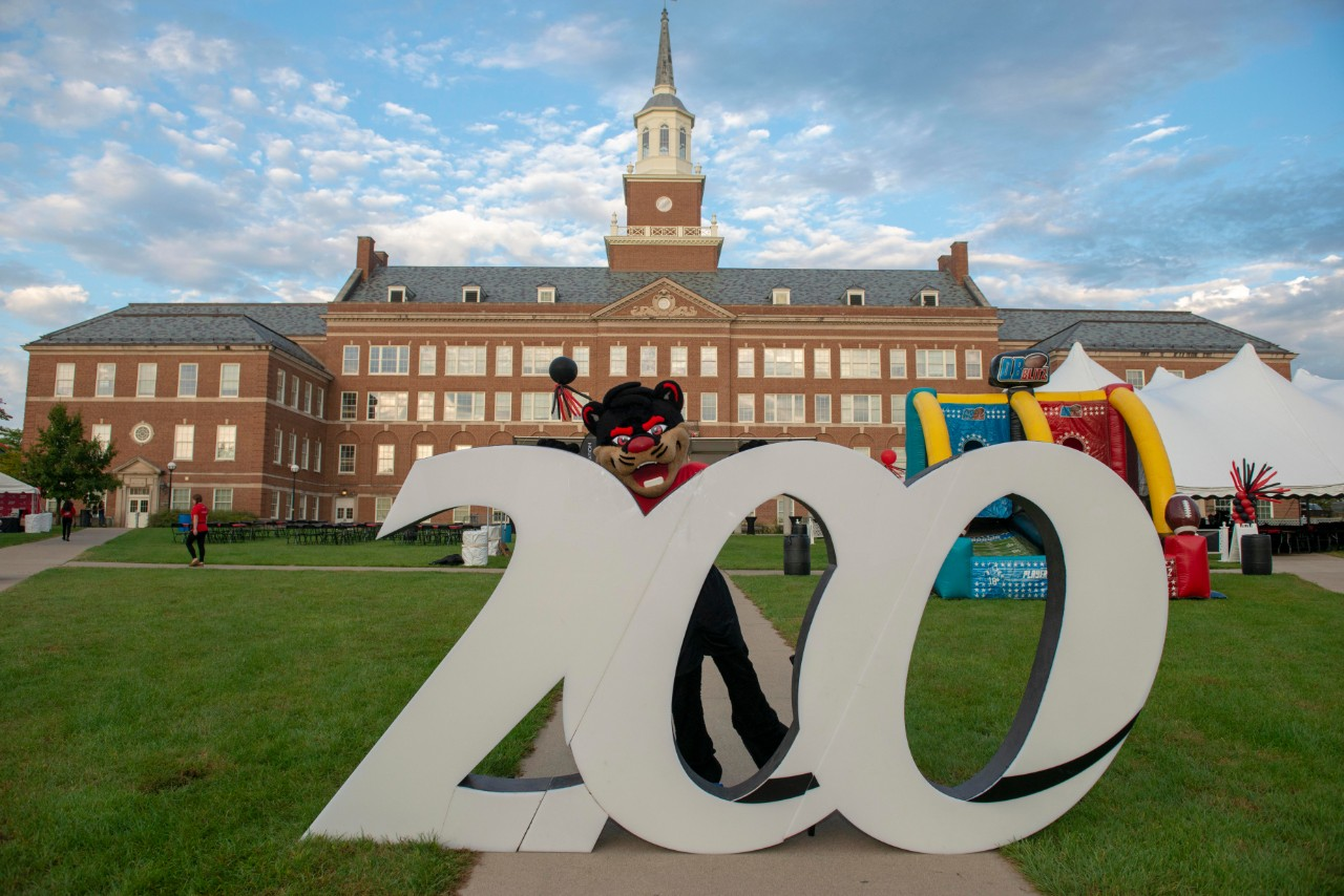 The Bearcat mascot poses with a Bicentennial sculpture