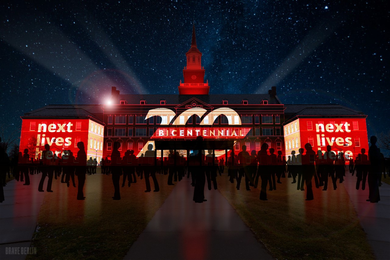 McMicken Hall featuring a projected image of the UC Bicentennial logo