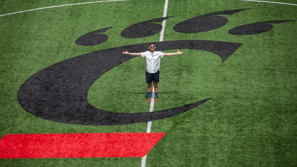UC student stands on the UC logo on the soccer field